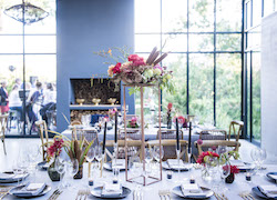 Dining table with brightly coloured flowers and dinner setting