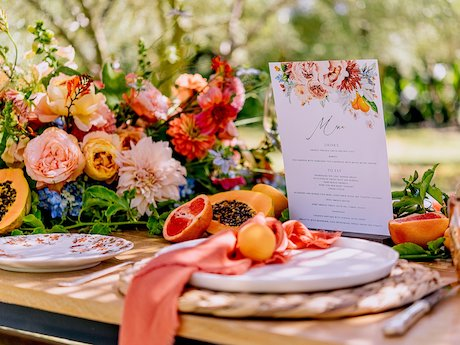 Brunch table set up with flowers and plates and glassware