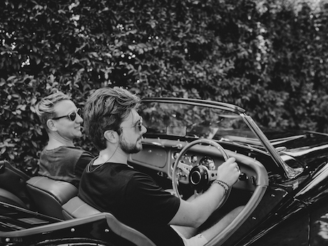 Groom and best man driving luxury classic car